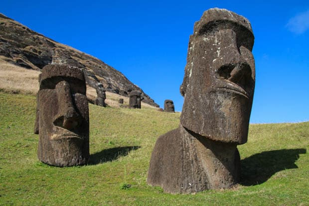 Two Moai statues in Easter Island, Chile with green grass and blue skies.