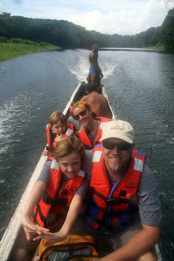 Family of travelers in a traditional wood carved motorized canoe on a river in Panama.
