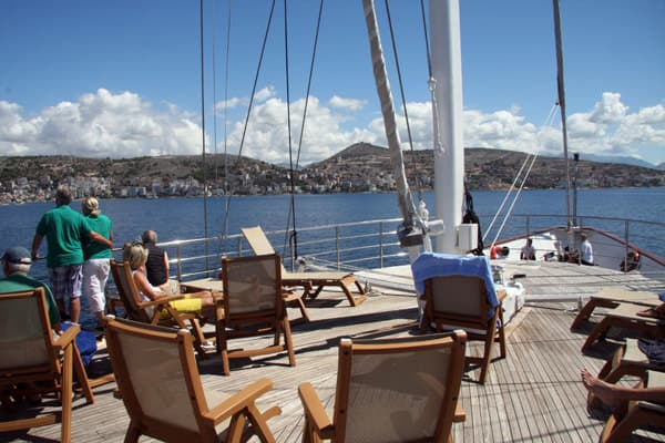 People lounging on the bow of their small ship cruising the Adriatic sea.
