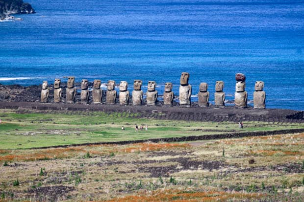 A line of Moai statues with the ocean in the background with visitors in the grass.