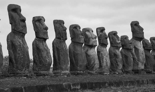 A line up of Moai Statues in black and white.