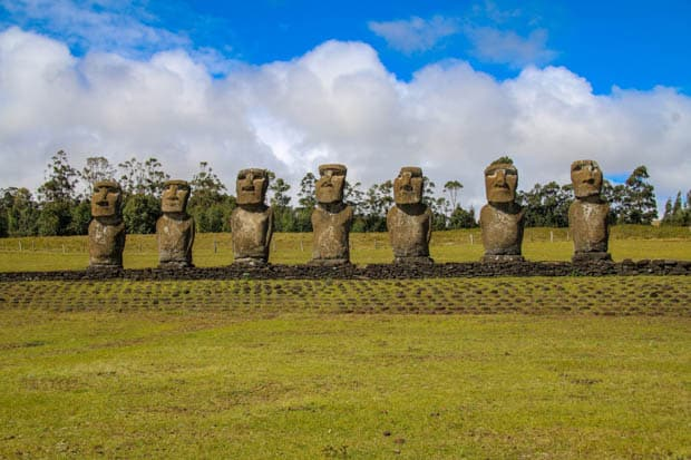 Moai statues lined up with green grass and big clouds.