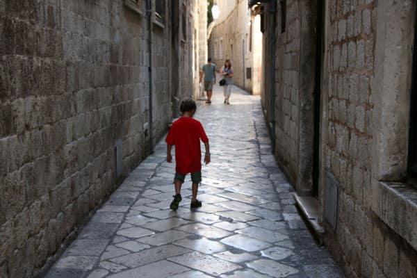 Child walking down marble alleyway in Dubrovnik Croatia.