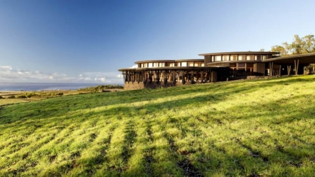 Explora Rapa Nui lodge with green grass in front of the lodge looking out over the ocean and landscape.