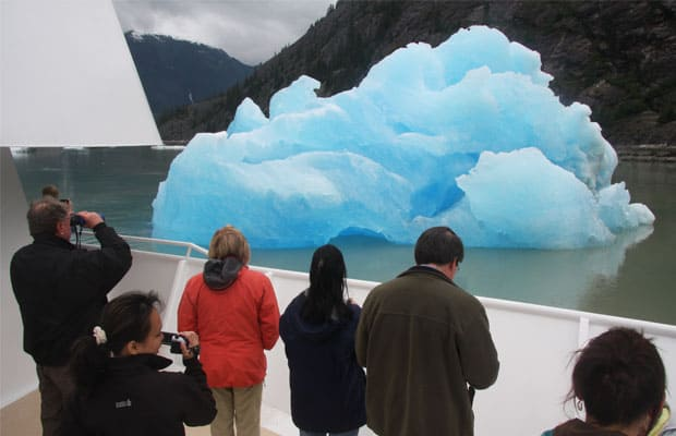 group of alaska small ship cruise travelers on the side of the boat taking pictures of a large iridescent blue piece of floating ice