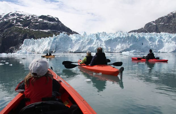 group of alaska small ship cruise travelers kayaking in front of a glacier on a sunny day