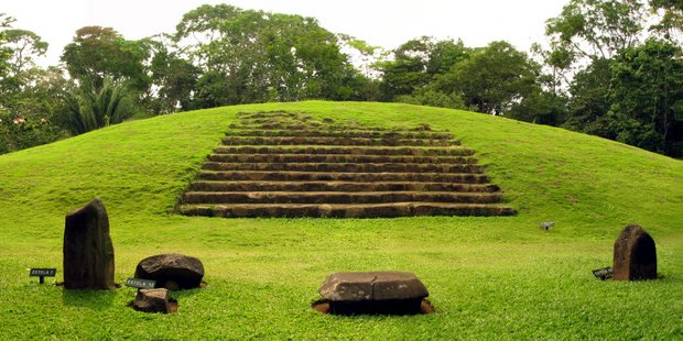Guatemalan ruin on a grassy knoll with stone staircase and rocky points.