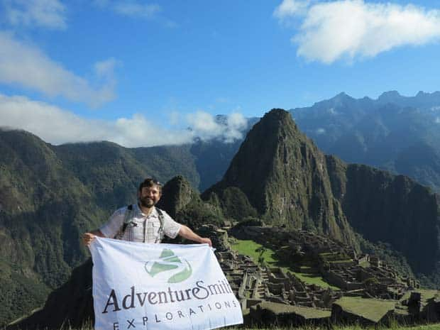Single traveler holding a Adventuresmith Explorations flag in front of Machu Pichu.