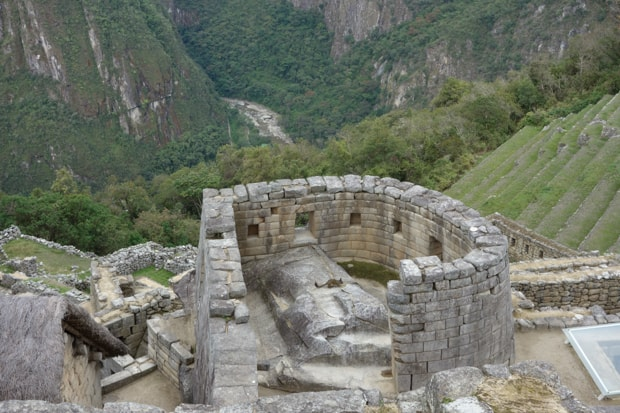 Stone building in the Machu Picchu ruin with terraced grassy areas and forest.