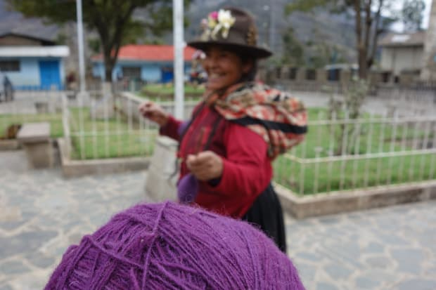 Purple yarn and a traditionally dressed Peruvian woman in a courtyard in a village.