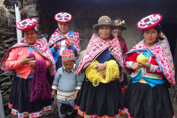 Peruvian ladies wearing hats and dressed in colorful traditional dress holding purple and yellow yarn.