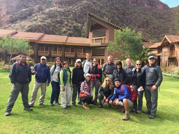 Group of travelers posing in front of a lodge on a land tour in Peru.