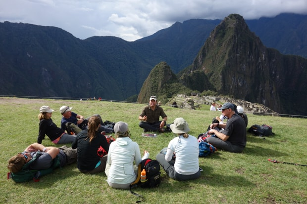 Group of travelers and guide sitting and snacking with Machu Picchu in the background.