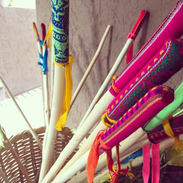 Eucalyptus hiking poles with colorful weaved textile as handles in a basket.