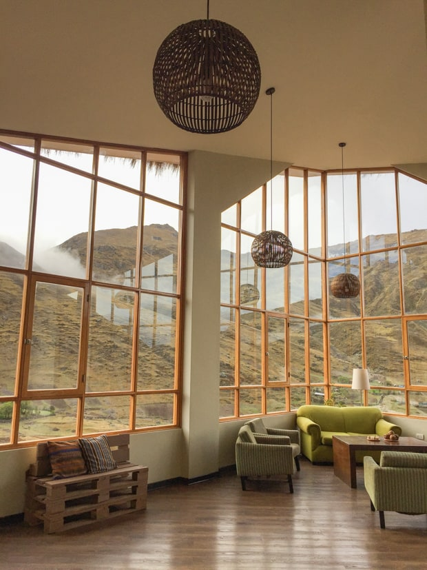 View of a lobby in a lodge with large windows looking a large mountain hillsides.
