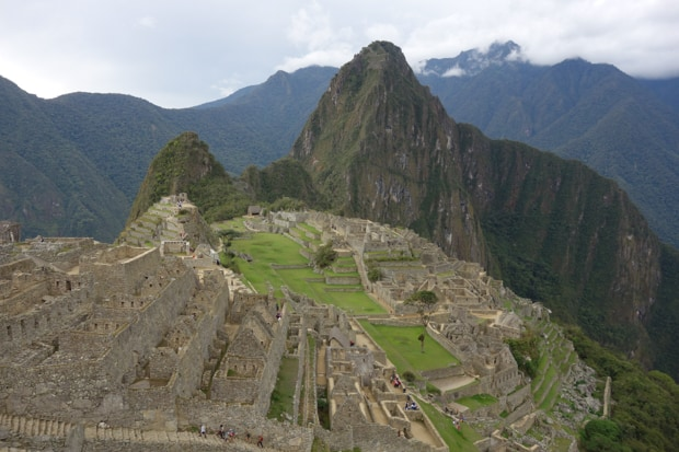View looking down of Machu Picchu with large mountains surrounding the ruin.