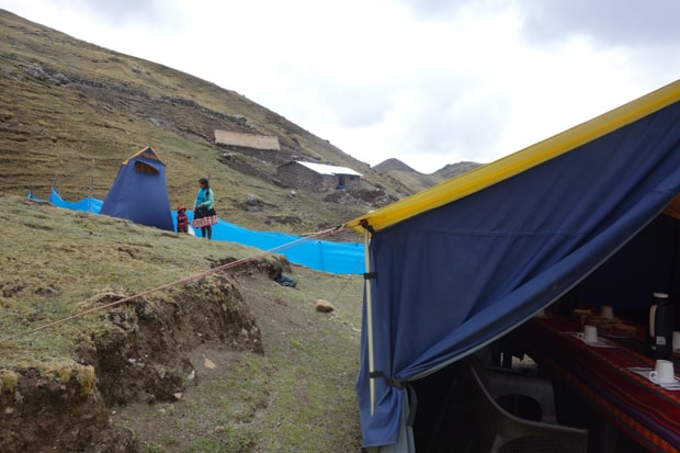 Blue tent with a long dining table with colorful textiles on a mountain hillside with a local mom and child dressed in colorful traditional Peruvian clothing.