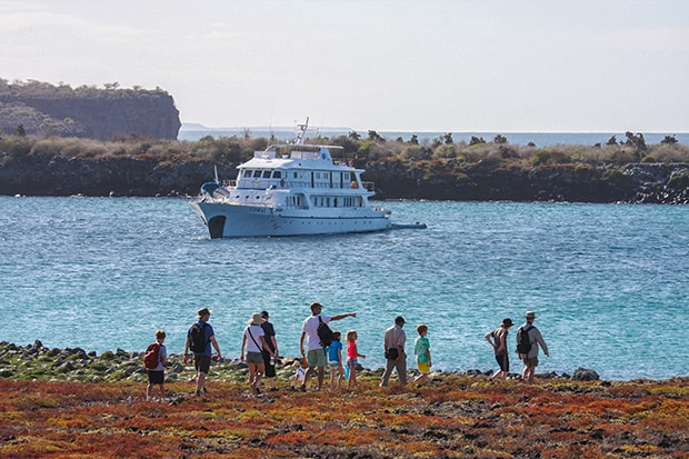 Families with children walking on shore in front of small ship in Galapagos.