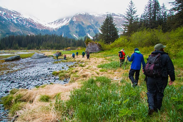 A group of Alaska travelers hiking along a creek.