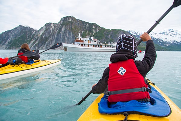 child kayaking in front of a small ship in Alaska on a family trip