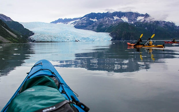 3 kayaks paddling in calm water viewing an Alaskan tidewater glacier.