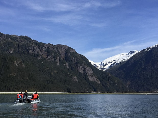 Alaska travelers in a skiff heading towards a beach under steep mountains in Alaska.