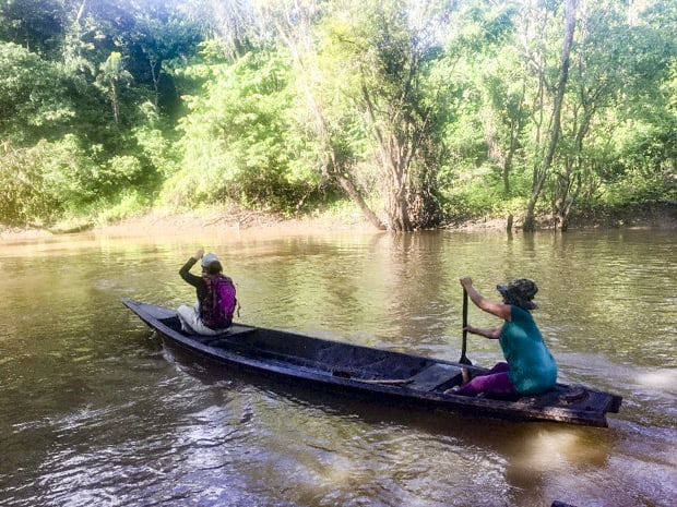 Two women paddling a canoe in the Peruvian Amazon river.