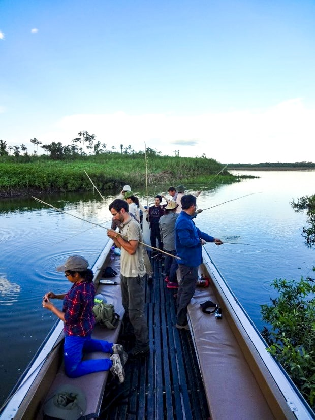 A group of people piranha fishing off a motorized canoe in the Peruvian Amazon jungle.