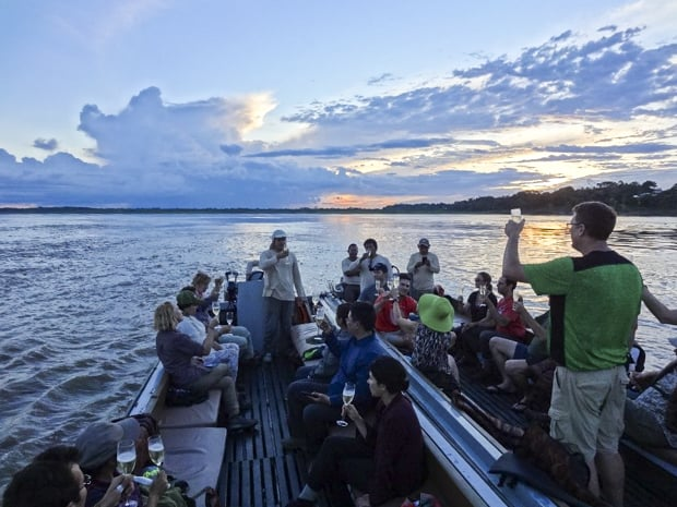 A group of people on a motorized canoe enjoying a champagne toast while the sun sets.