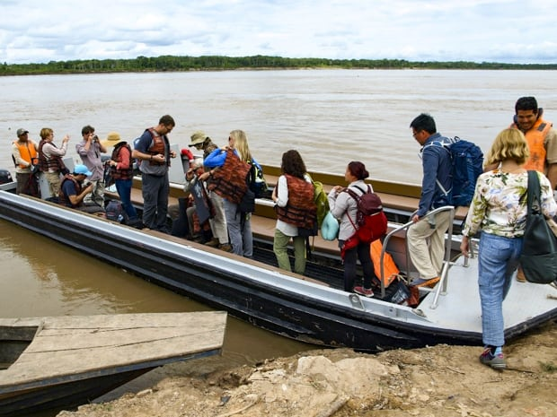 A group of people boarding a motorized canoe on the Peruvian Amazon jungle.