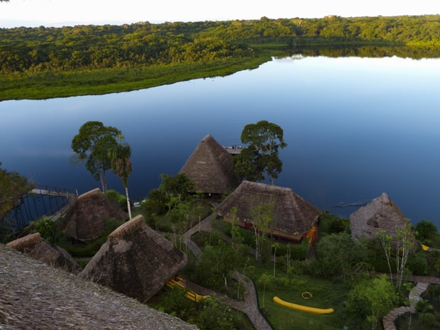 View of Napo from above of thatched roof huts and gardens with the river and jungle in the background.