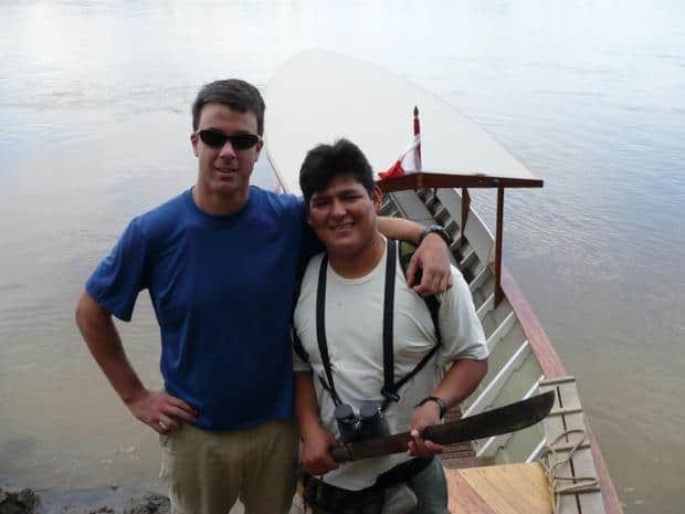 a traveler and guide holding a machete in front of a small open air boat.