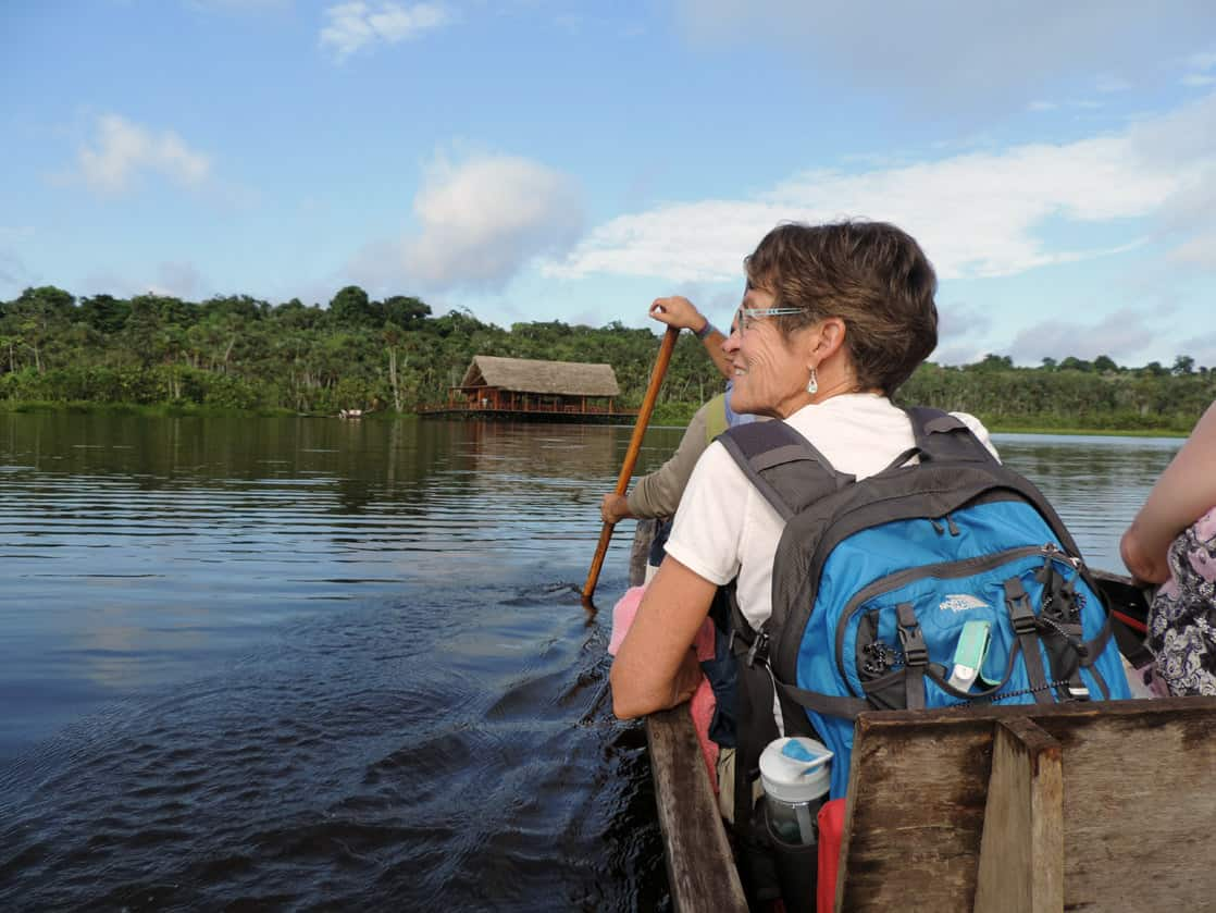 Travelers in a wooden canoe viewing the Amazon jungle from the water.