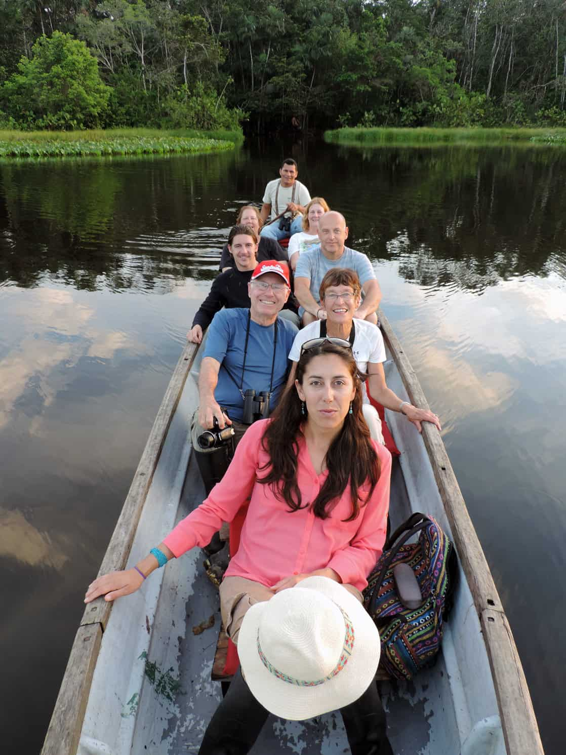 A group of Amazon travelers in a wooden canoe floating on a river in the Amazon.