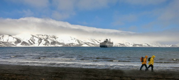 Two passengers on a land excursion in Antarctica walking along the shore with their small ship in the background.
