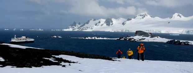 People cross country skiing on Antarctica with their small ship cruise in the background.