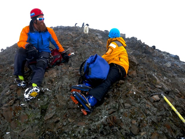 Guests taking a break on their mountaineering excursion next to penguins in Antarctica.