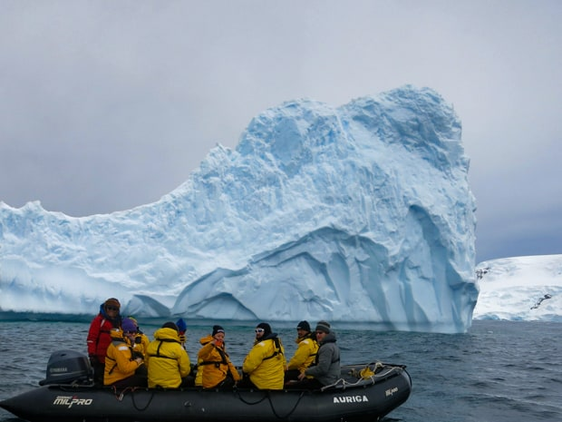 Guests from small ship on a skiff tour getting close to icebergs in Antarctica.