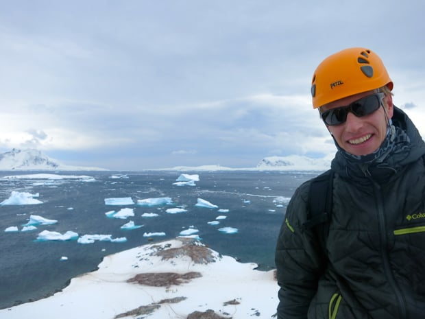 Happy guest from a small ship expedition smiling with icebergs in the background.