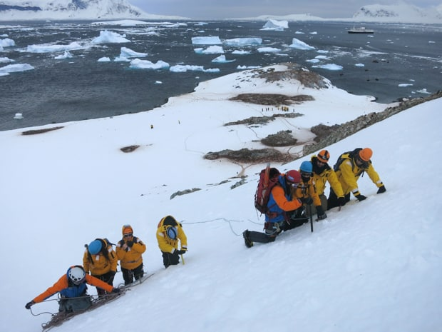People on a mountaineering excursion in Antarctica climbing uphill on snow with ice picks and ropes with their small ship in the background.