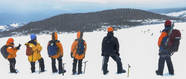 Group taking a break from their mountaineering excursion and looking at the view from where they climbed in Antarctica.