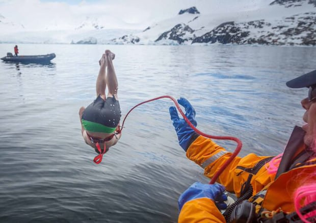 Guest with safety rope attached jumping off a small ship during a polar plunge event in Antarctica.