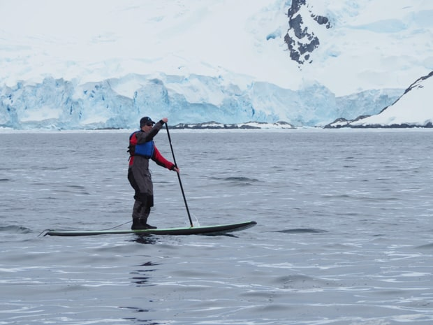 Guest from a small ship stand up paddleboarding in a drysuit in Antarctica.