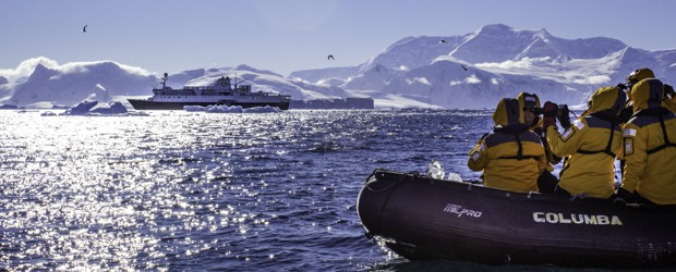 People on a skiff excursion taking a picture of their small cruise ship dwarfed by the snowy landscape of Antarctica.