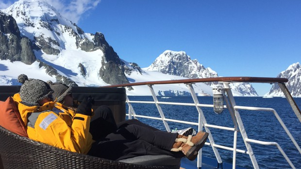 Guests lounging in the sun on a sofa bed outside on deck of their small ship cruise in Antarctica.