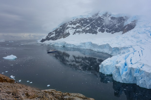 View from a hike of the ice shelf in Antarctica with small ship in the bay.