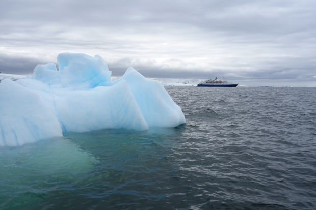 Small expedition ship cruising through Antarctica with iceberg in the foreground.