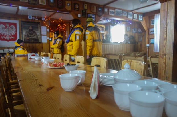 Guests from a small ship cruise have coffee inside the polish research station in Antarctica.