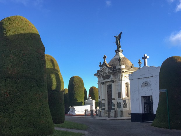 Cemetery in Punta Arenas, Chile with a mausoleum surrounded by tall landscaped trees.