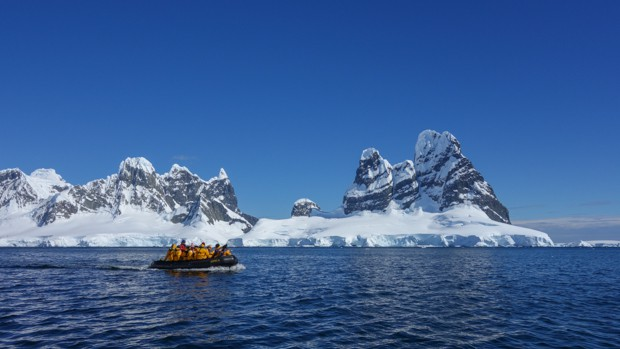 Guests from a small ship on a skiff tour going to land in Antarctica.